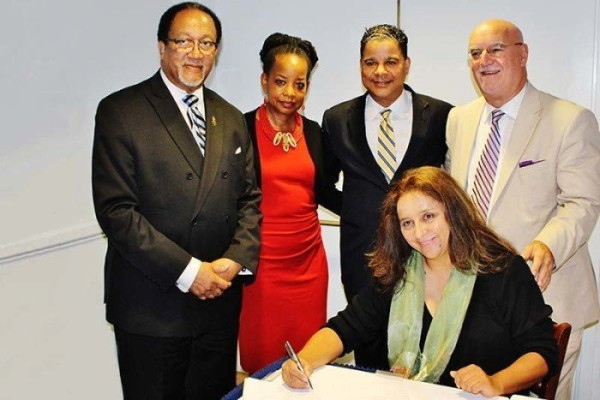 NNPA National President Dr. Benjamin F. Chavis, NNPA Board Chair Denise Rolark Barnes, NNPA First Vice President Francis Page, and NAHP Manager Jose Sueiro observe NAHP Vice President Martha Montoya adding the final signature to their Task Force Proclamation that was signed in both English and Spanish versions. (Photo credit: Malcolm Lewis Barnes)